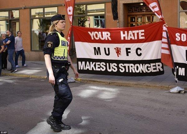 Một nữ cảnh sát đi qua tấm băng rôn của fan M.U